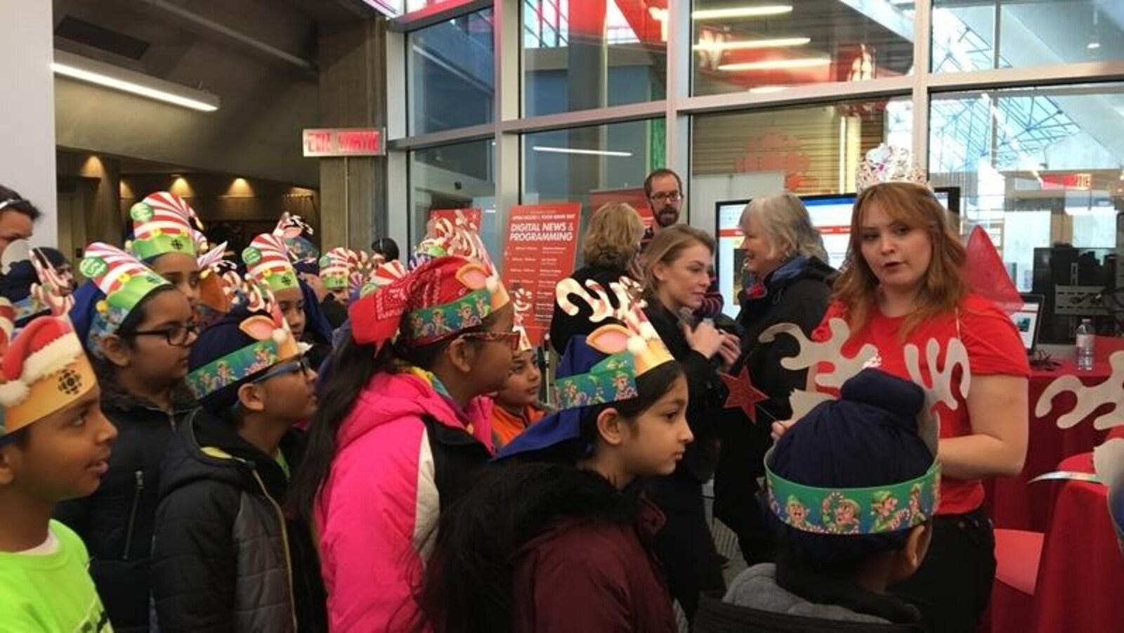 Des enfants écoutent la reporter météo Sarah Murphy dans la salle de nouvelle de Radio-Canada