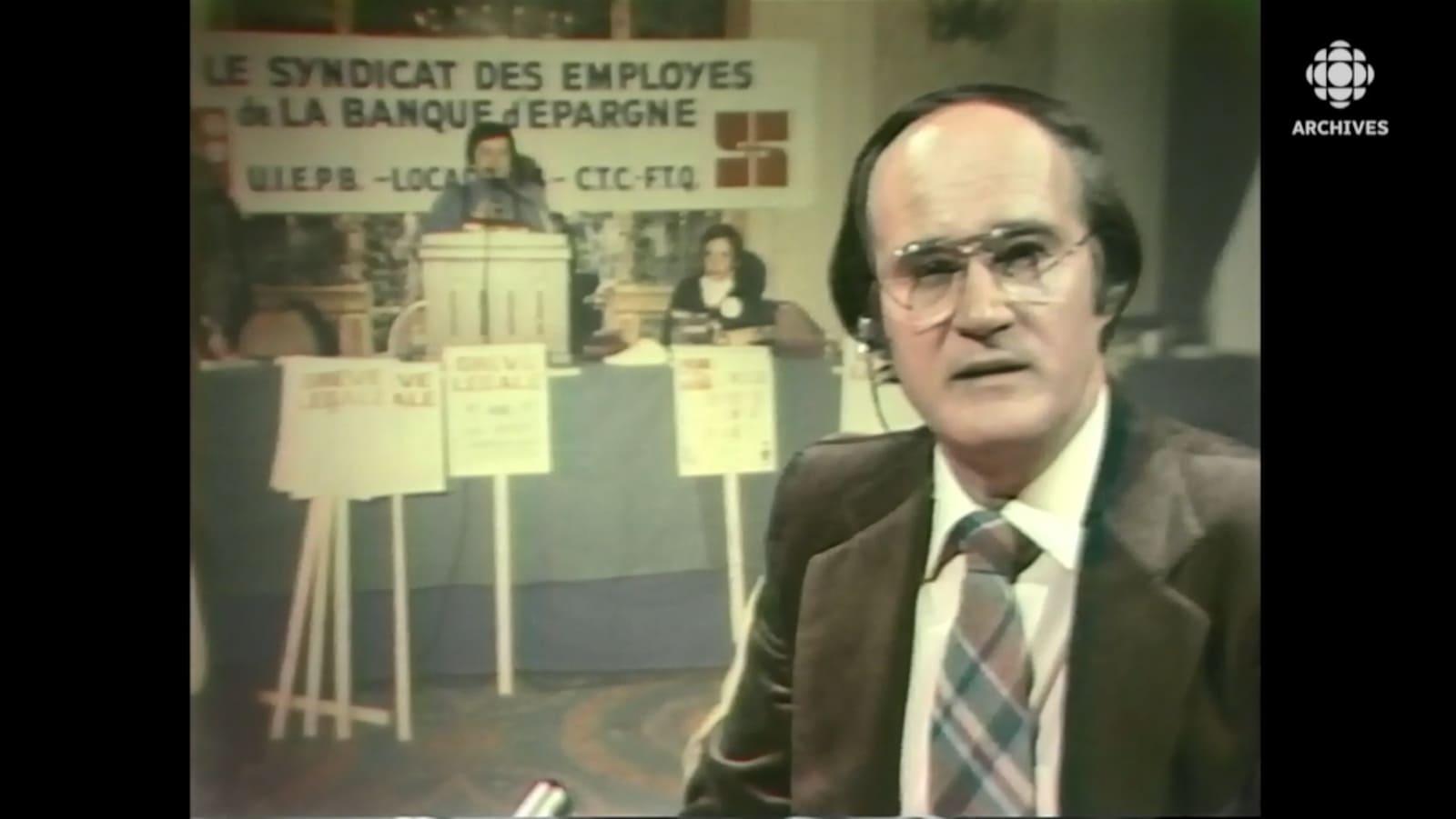 Le présentateur Gabi Drouin devant une mortaise d'une photo de l'assemblée de grève.