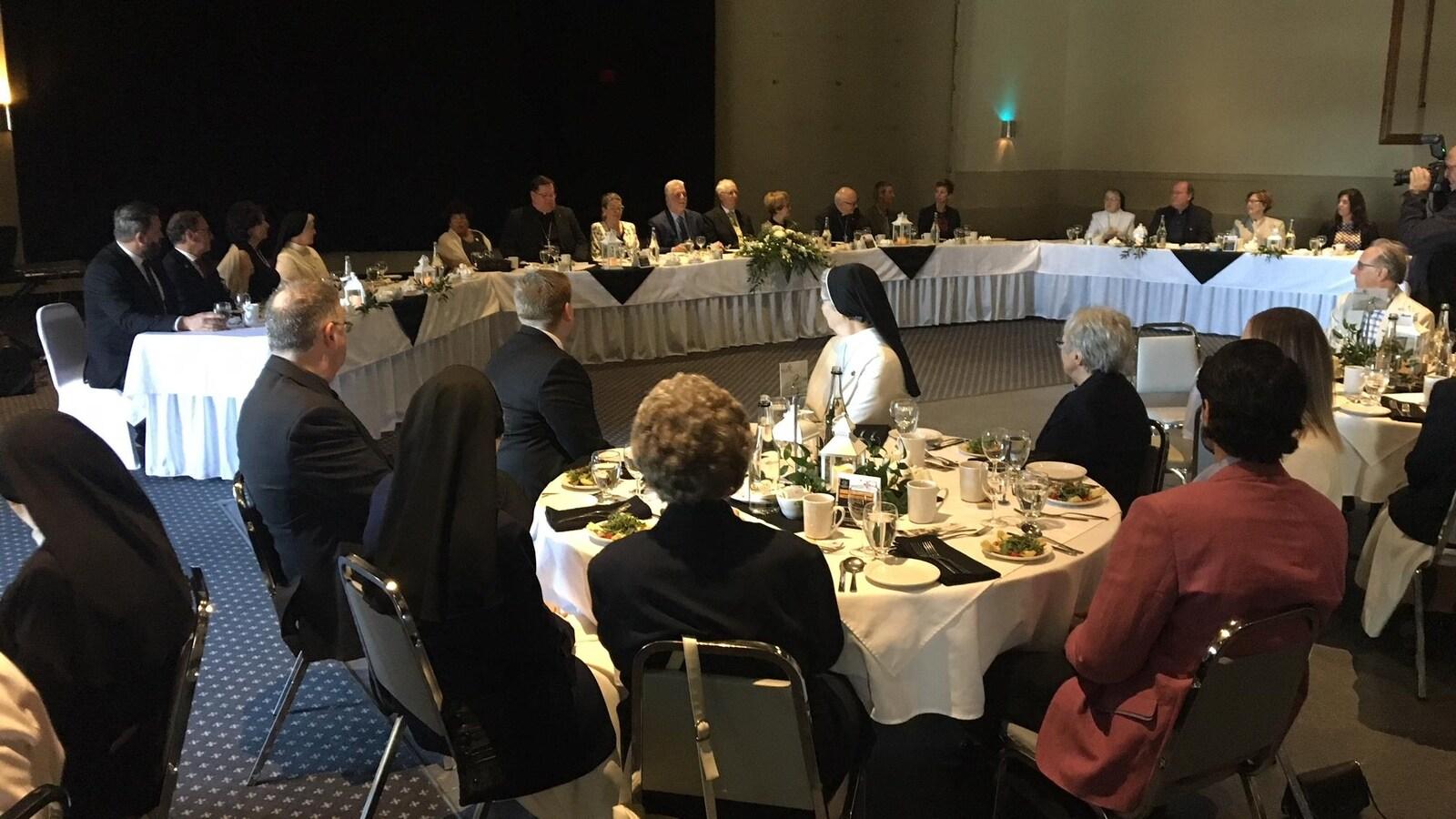 Des gens attablés devant une table d'honneur regroupant les dignitaires invités.