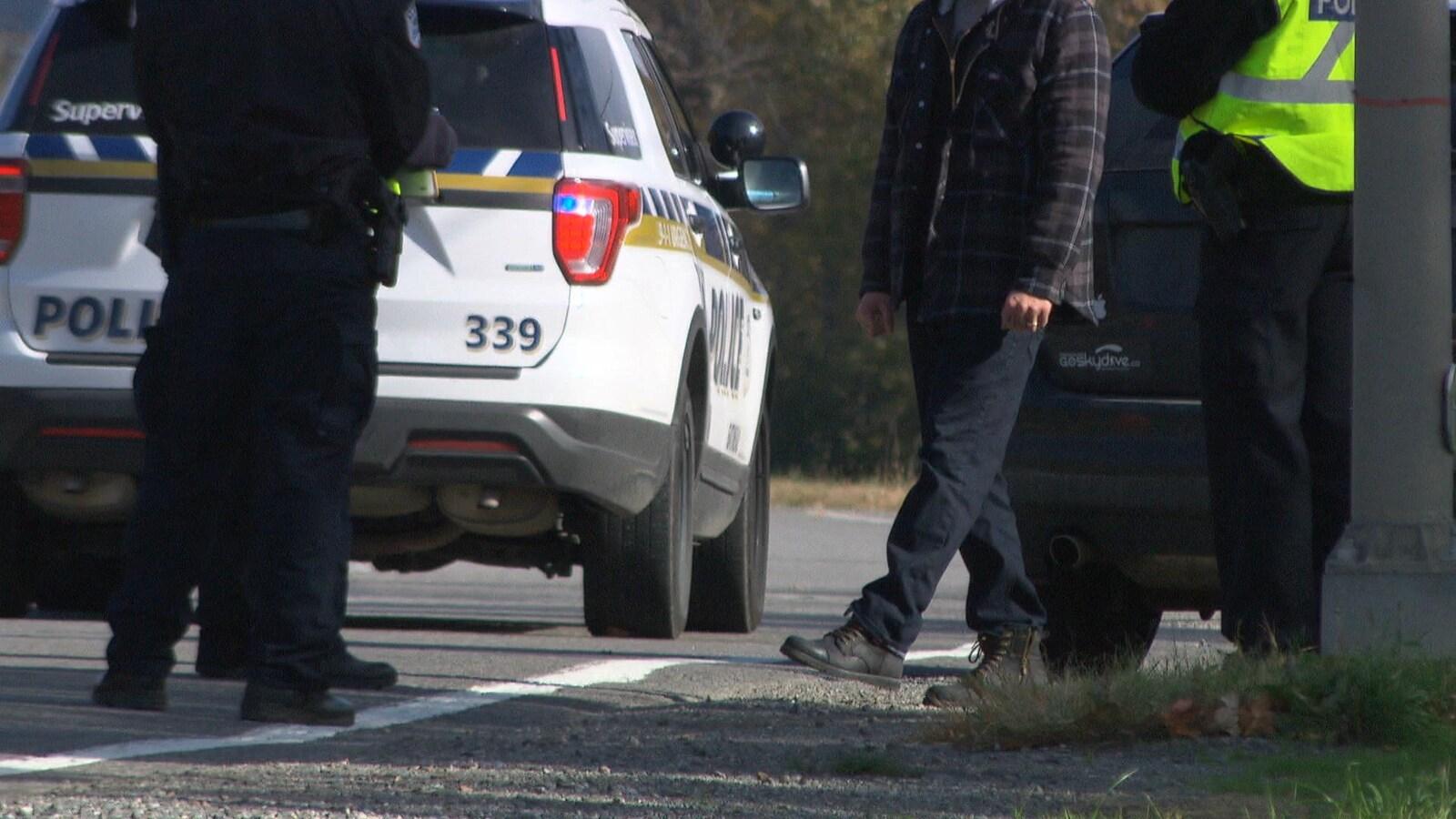 Un homme inconnu lève sa jambe gauche pour tester son équilibre devant trois agents du Service de police de la Ville de Gatineau en bordure de la route.