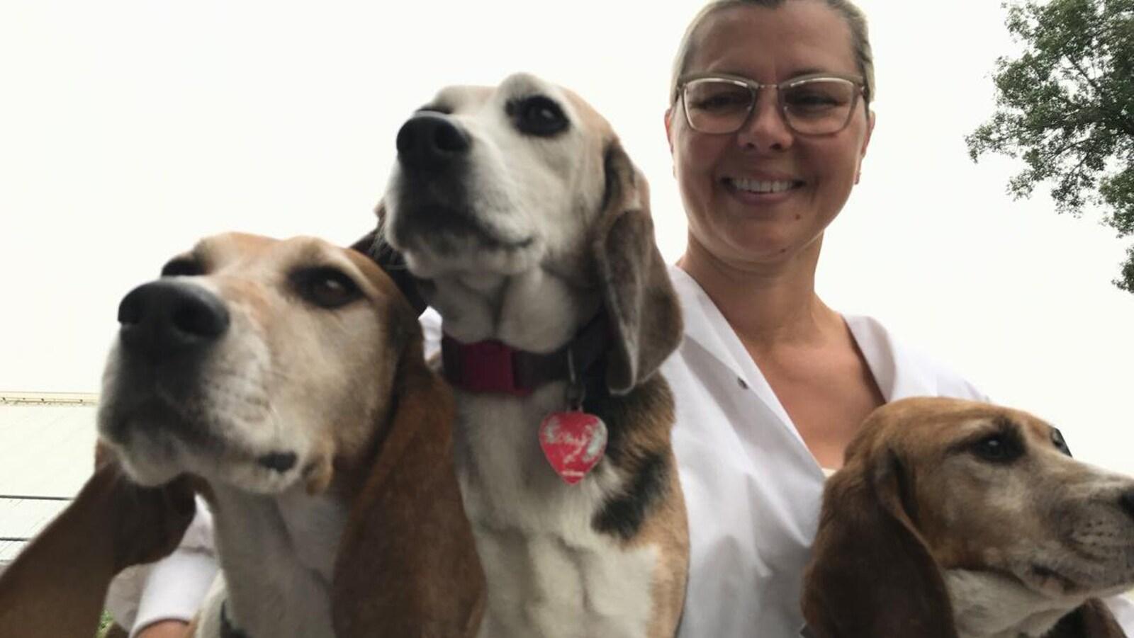Vue en contre-plongée sur trois beagles qui regardent au loin et une scientifique avec blouse et lunettes qui regarde l'objectif.