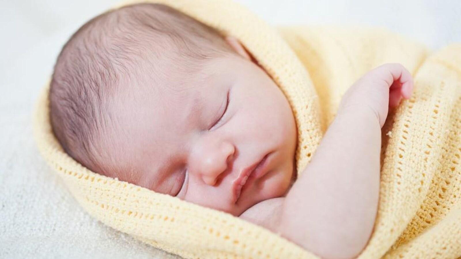 Un bébé nouveau-né dort, enveloppé dans une couverture.