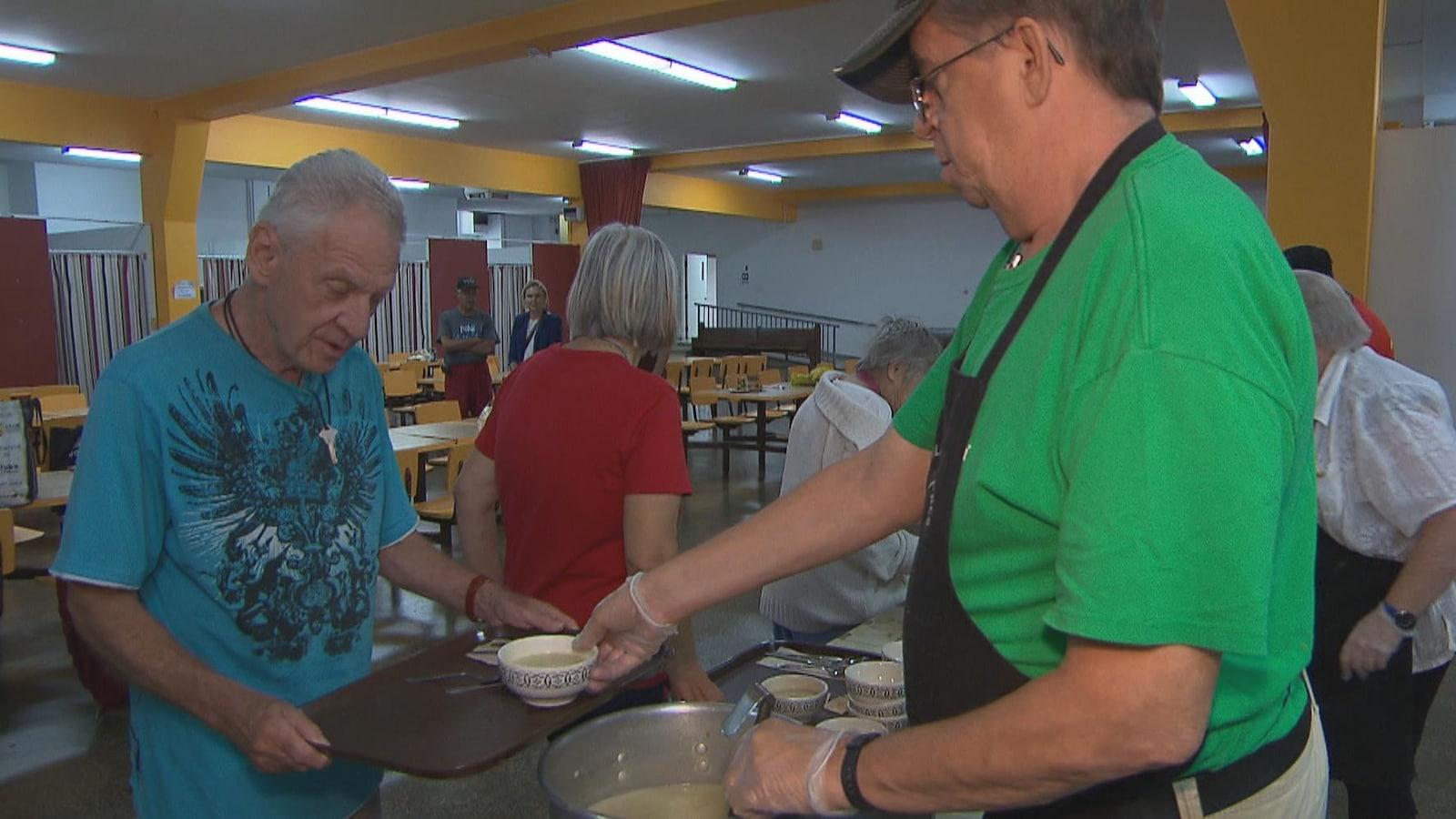 Un bénévole de la Tablée des nôtres sert un bol de soupe à un bénéficiaire.