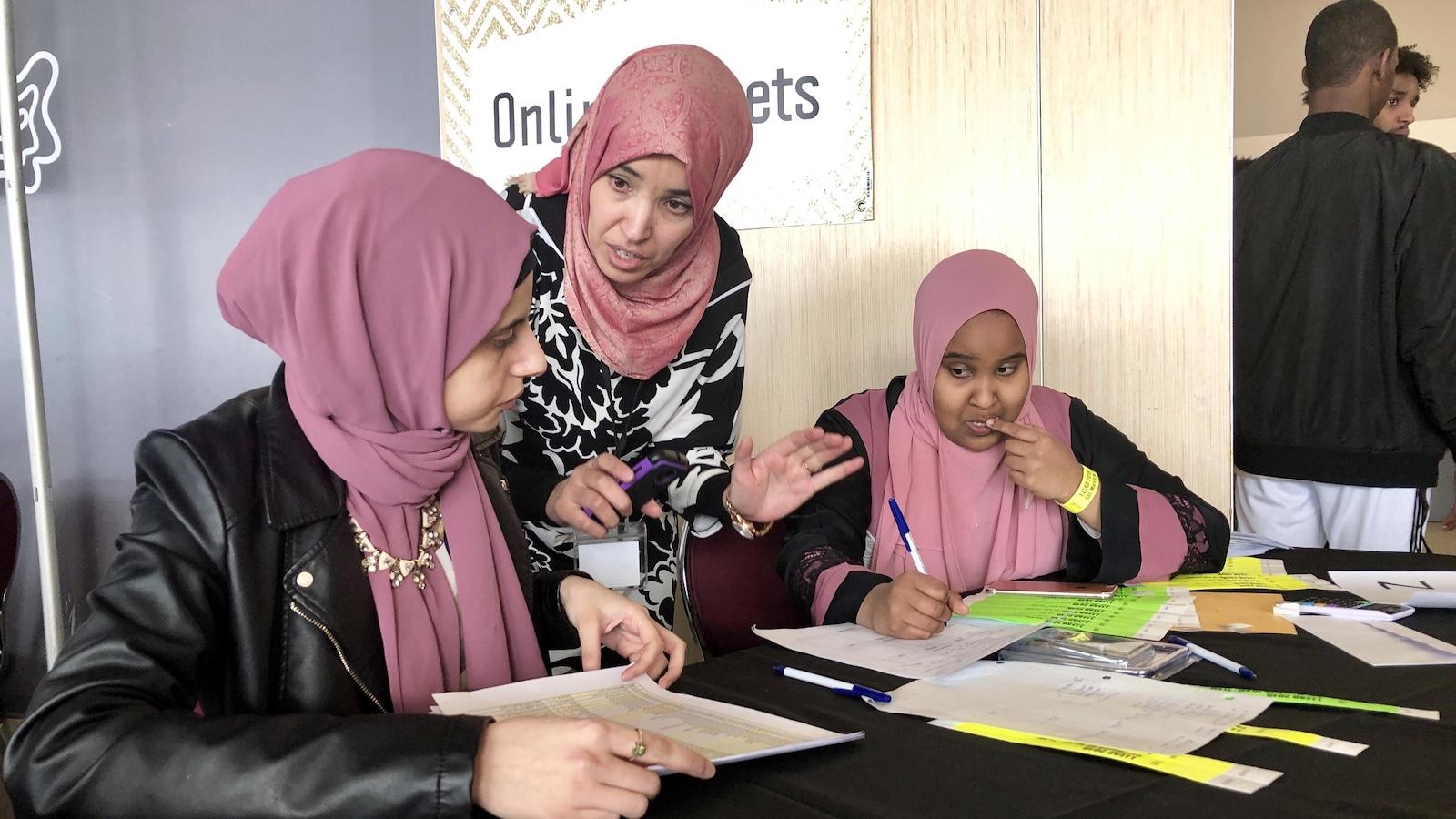 Trois femmes assises à une table en train d'étudier des listes de noms.
