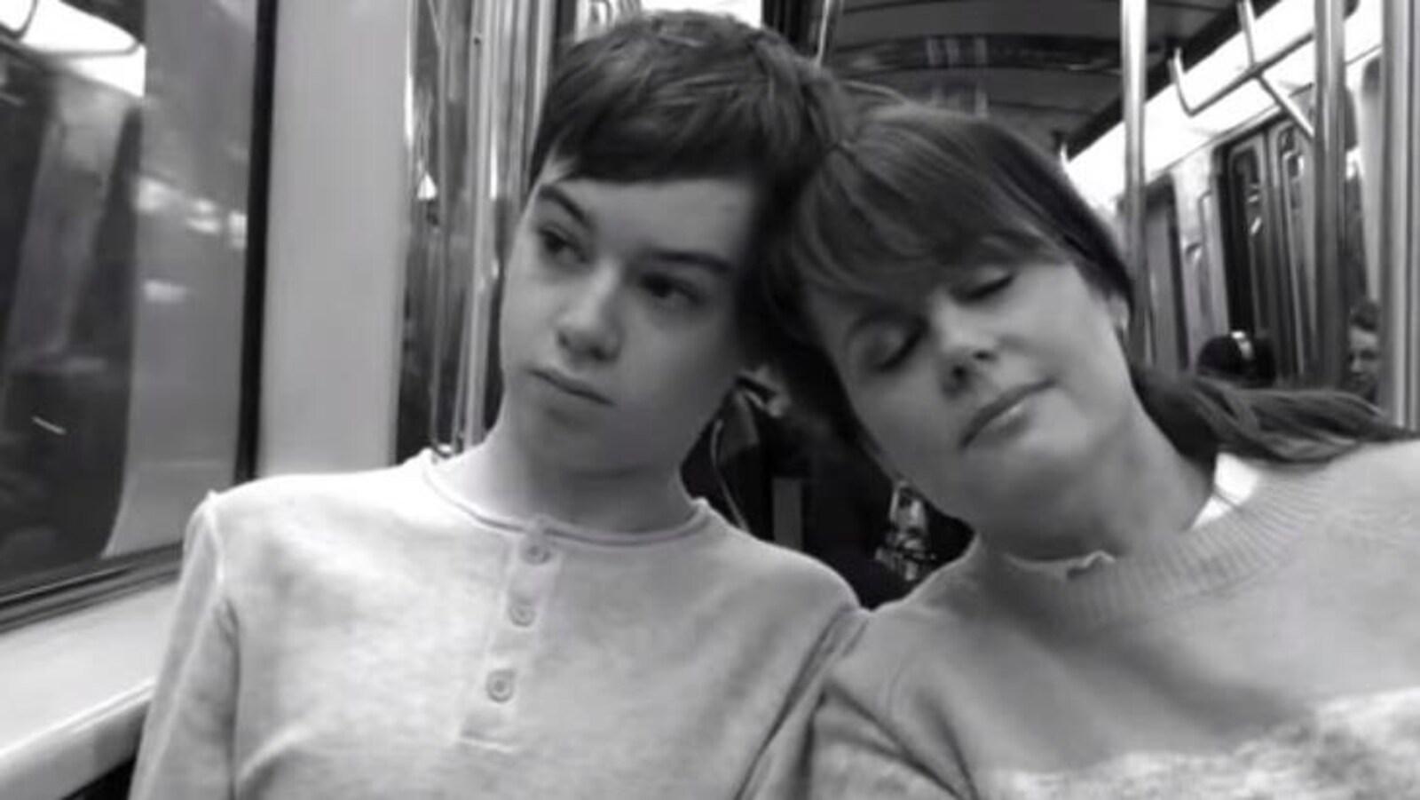 Le jeune homme et sa mère sont collés assis dans le métro.