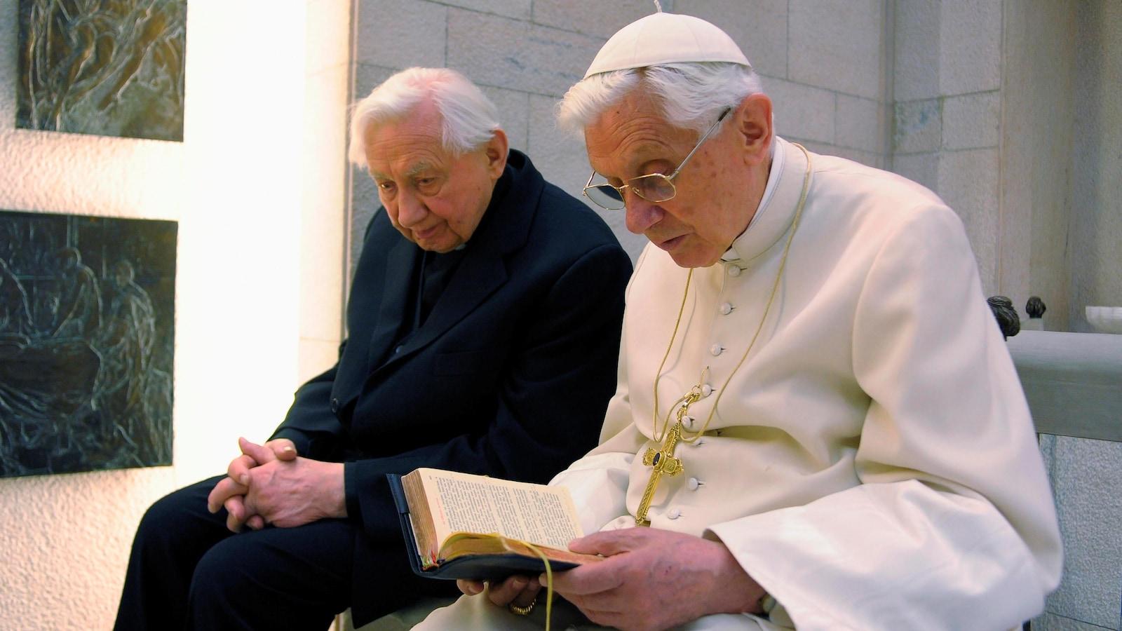 Le pape Benoît XVI (à droite), qui a quitté ses fonctions en février 2013, prie avec son frère Mgr Georg Ratzinger dans sa chapelle privée au Vatican, le 14 avril 2012.
