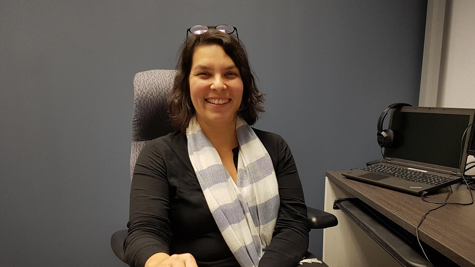 Assise à un bureau, Mme Mollen Dupuis sourit à la caméra.