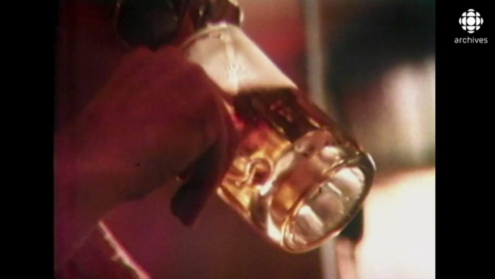 Un homme non reconnaissable boit une bière dans un gros verre.