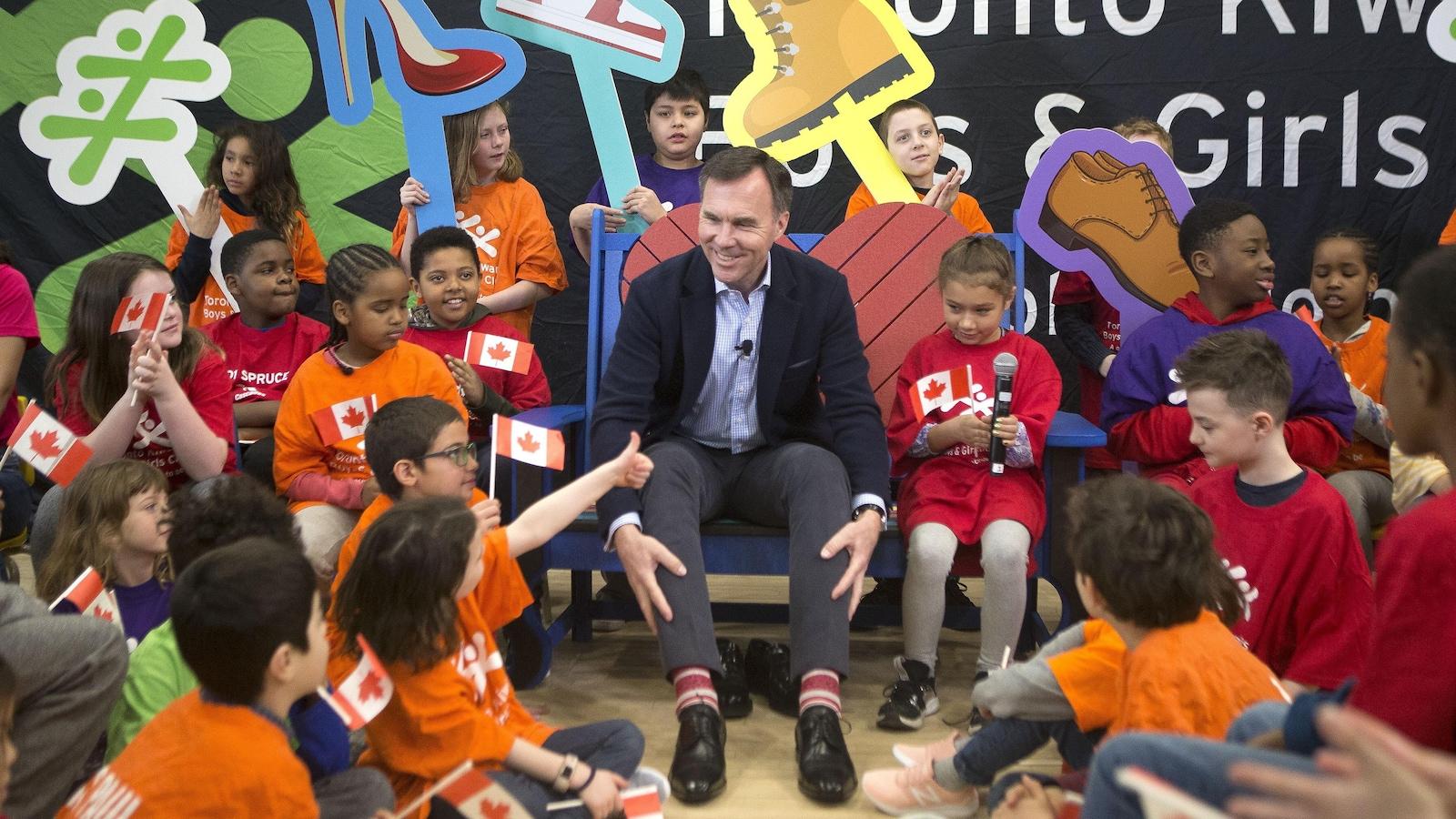 Le ministre Morneau est entouré d'enfants et il essaie des souliers.