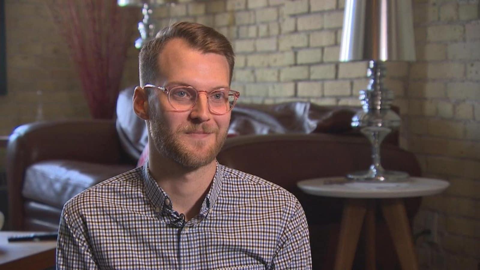 Un jeune homme blond à lunettes, dans un salon.