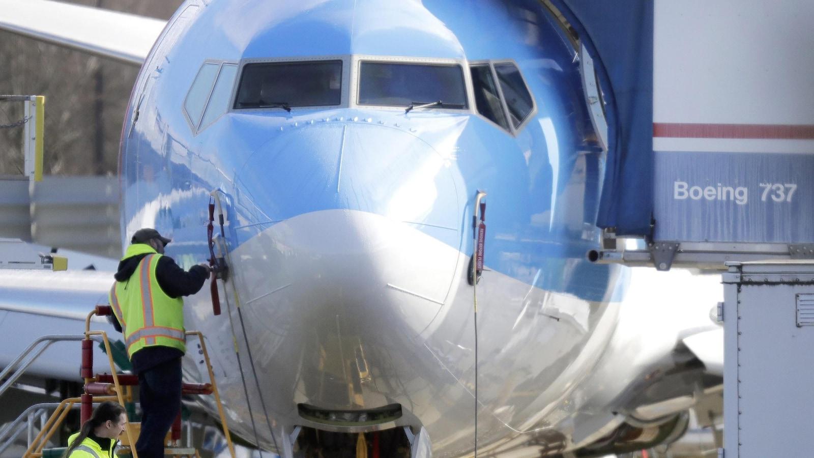 Un travailleur se tient sur une plate-forme près d'un avion Boeing 737 MAX 8 en construction pour TUI Group à l'usine d'assemblage Renton de Boeing Co. à Renton, Washington