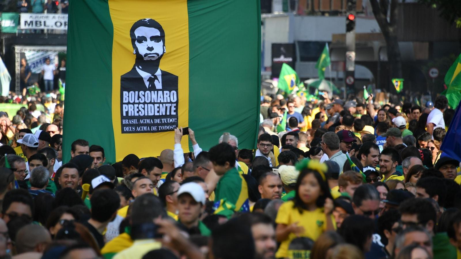 Des supporters de M. Bolsonaro tiennent une pancarte sur laquelle est écrit : « Bolsonaro président ».
