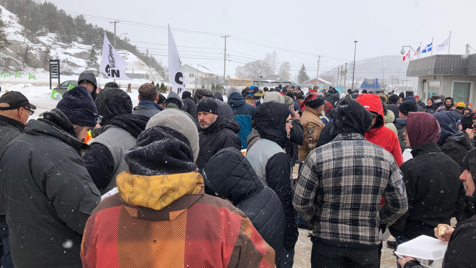 Plusieurs personnes sont rassemblées à l'extérieur de l'usine Bombardier.