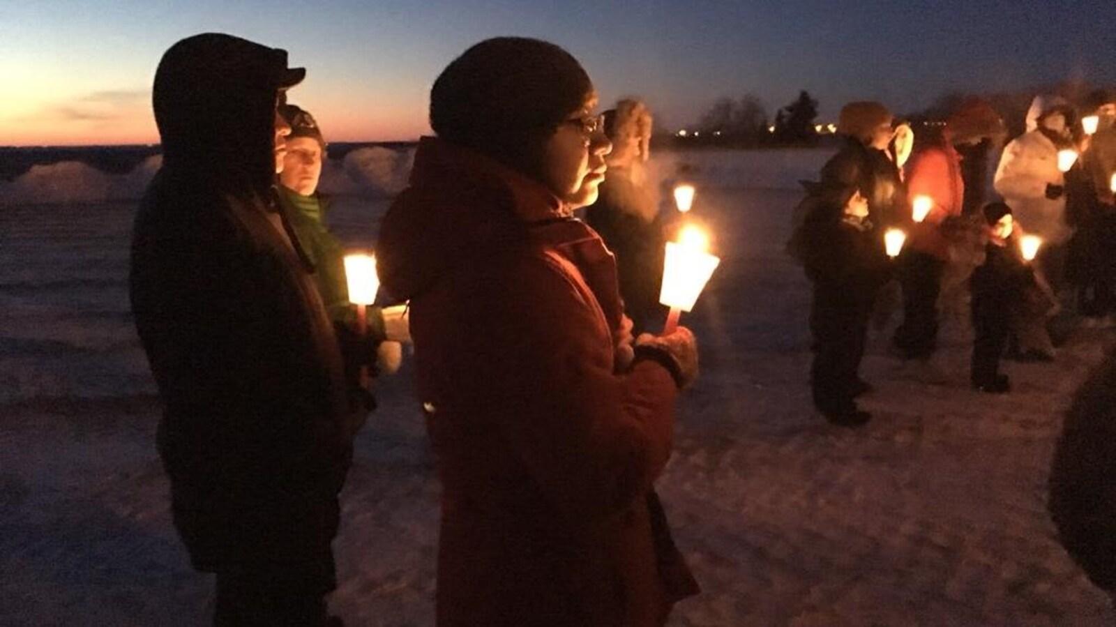 Une dizaine de personnes tiennent debout dans leurs mains des bougies à la tombée de la nuit.