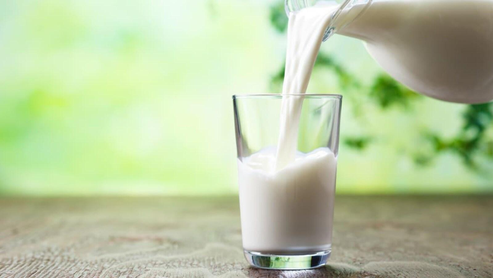 Une bouteille de lait remplit un grand verre.