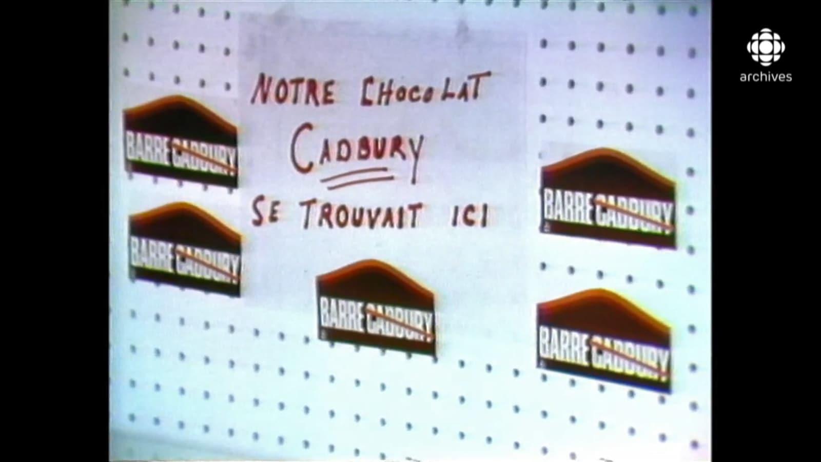 Étagère vide avec des autocollants de la campagne « On barre Cadvury » et une enseigne indiquant « Notre chocolat Cadbury se trouvait ici ».