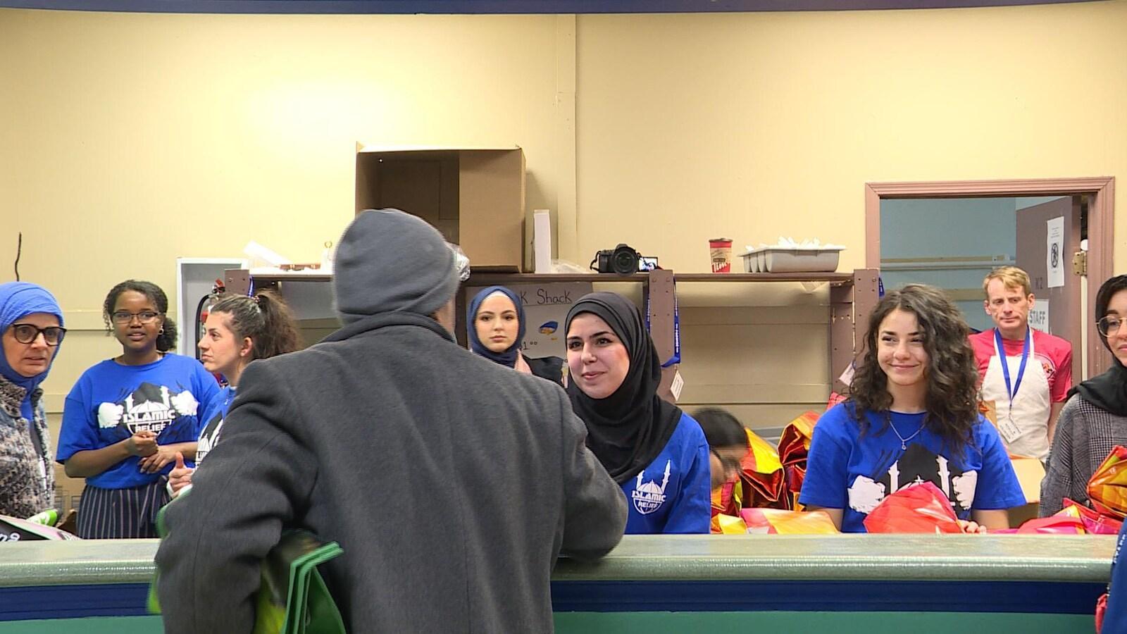 Des bénévoles d'Islamic Relief Canada, certaines portant le hijab, d'autres non, distribuent une trousse à un client du centre communautaire.