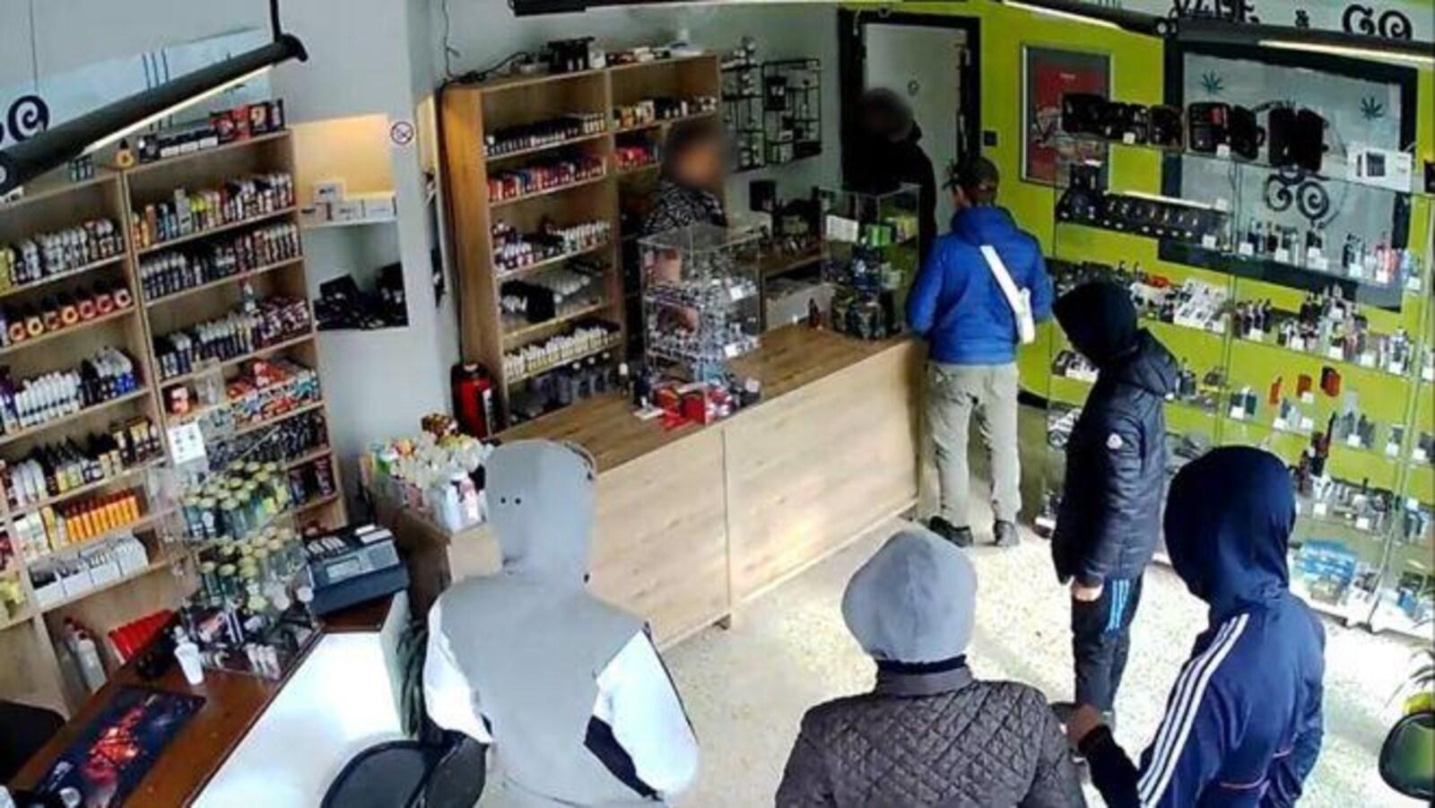 Dans un magasin, on distingue des cigarettes électroniques. Cinq individus, capuche sur la tête et le dos tourné, font face à un vendeur.