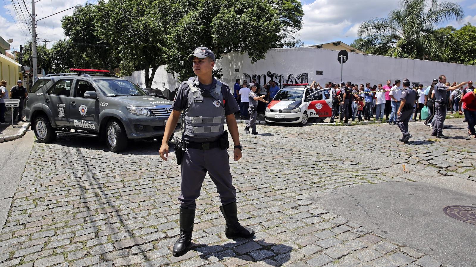 Des policiers montent la garde devant l'école publique Raul Brasil de Suzano, dans l'agglomération de Sao Paulo, au Brésil, où une fusillade a eu lieu le mercredi 13 mars 2019.