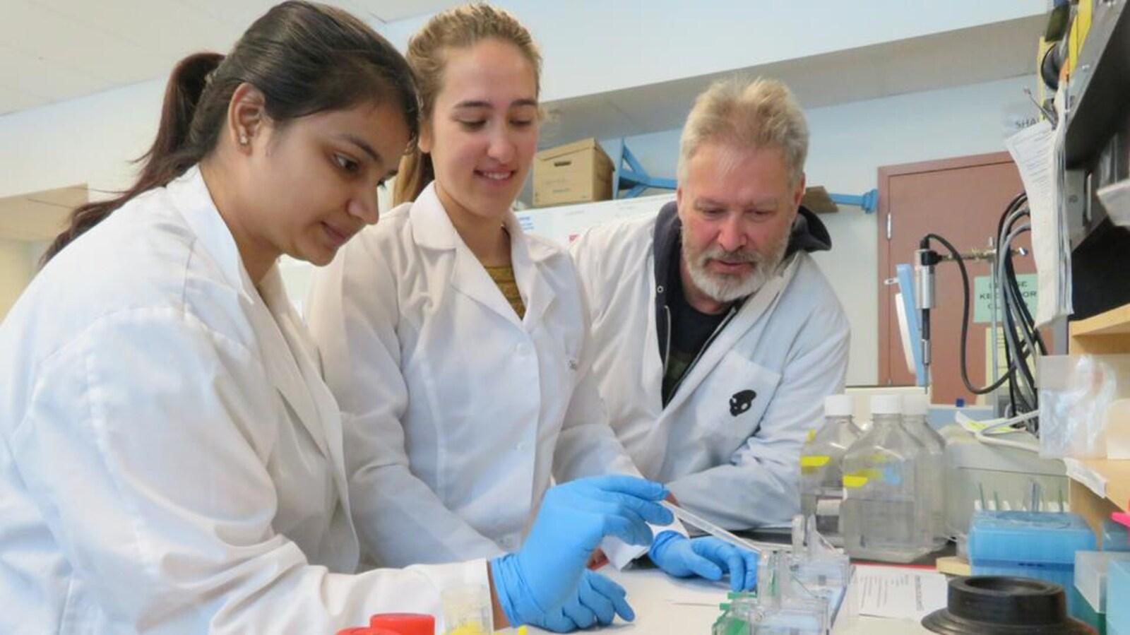 Un homme et deux femmes en sarau blanc remplissent une éprouvette.