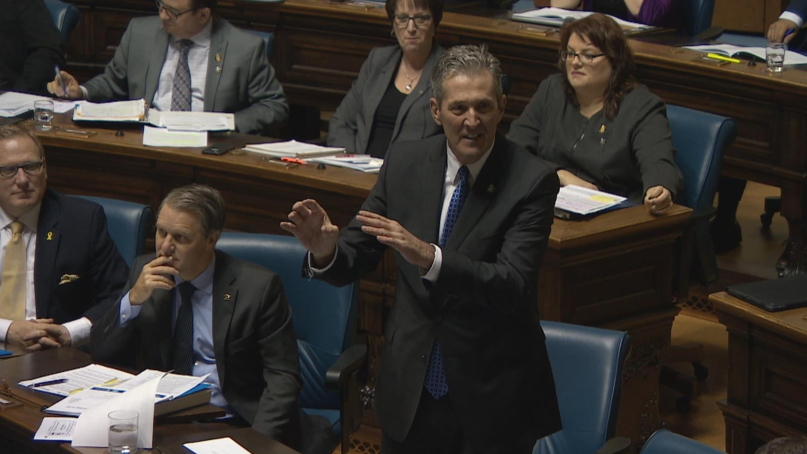 Pallister, debout en chambre, agite les mains en répondant à une question. À côté de lui, des ministres du gouvernement sont assis et écoutent.