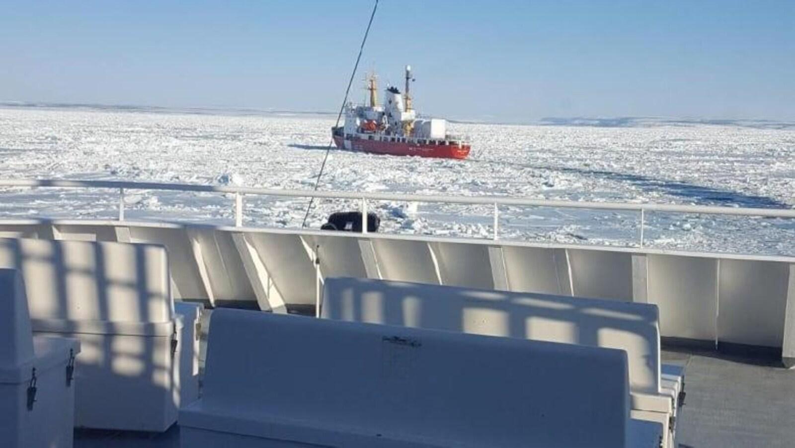 Un brise-glace dans un océan gelé photographié du pont d'un bateau.