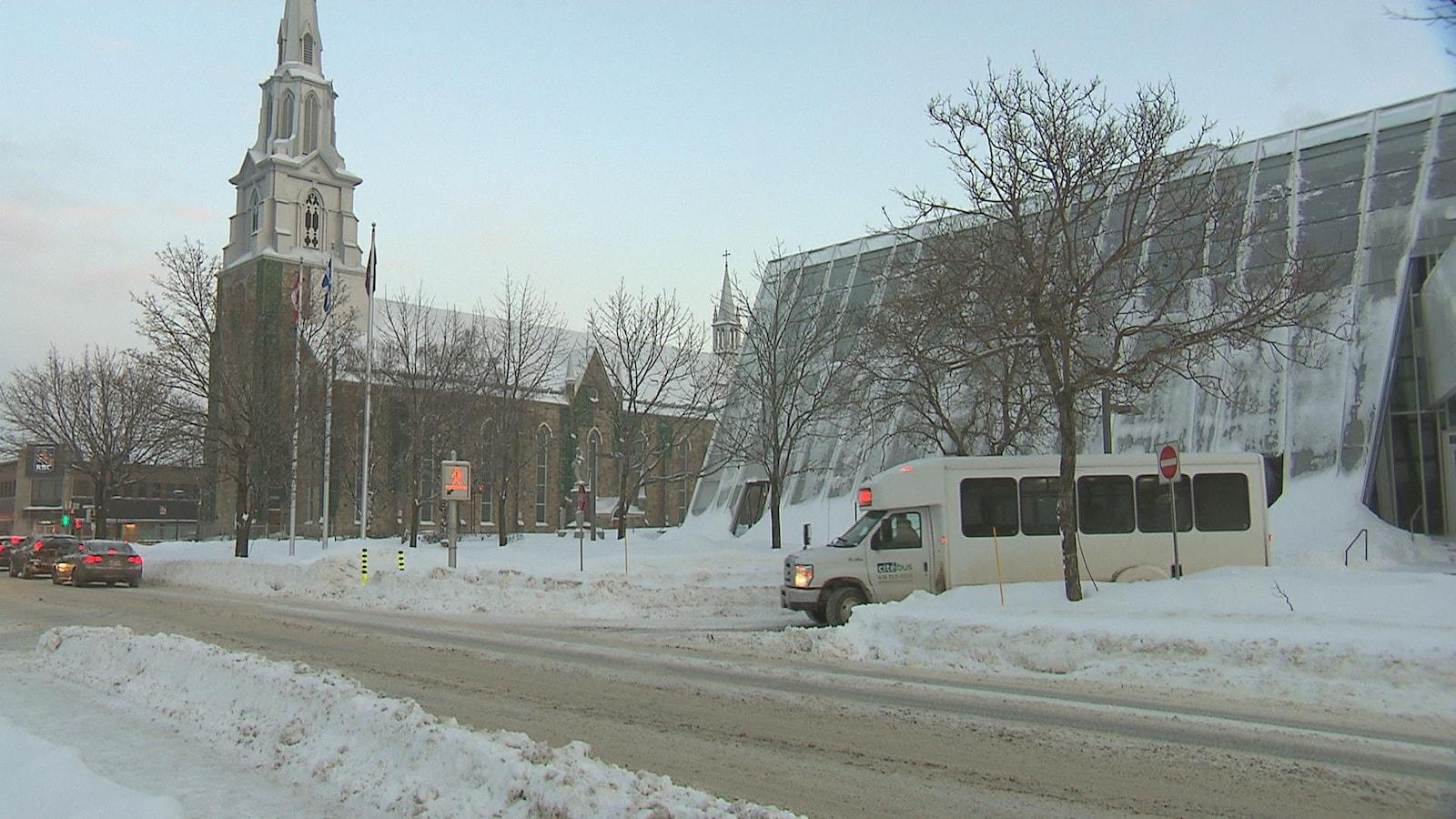 Un autobus de transport adapté à Rimouski circule dans une rue enneigée.