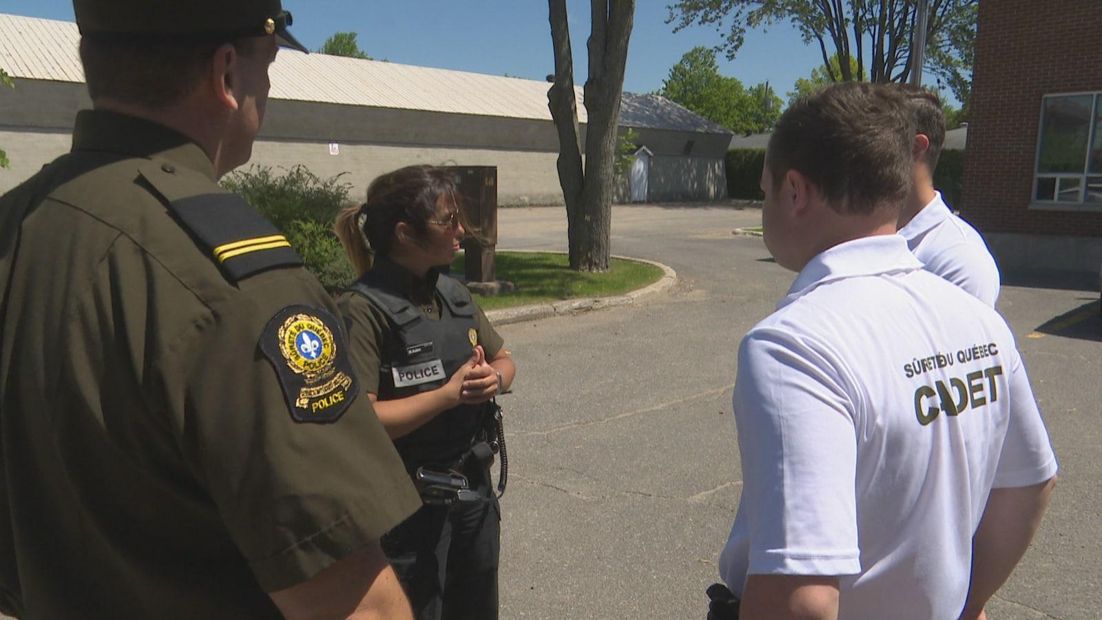 Des cadets et des policiers de la SQ discutent.
