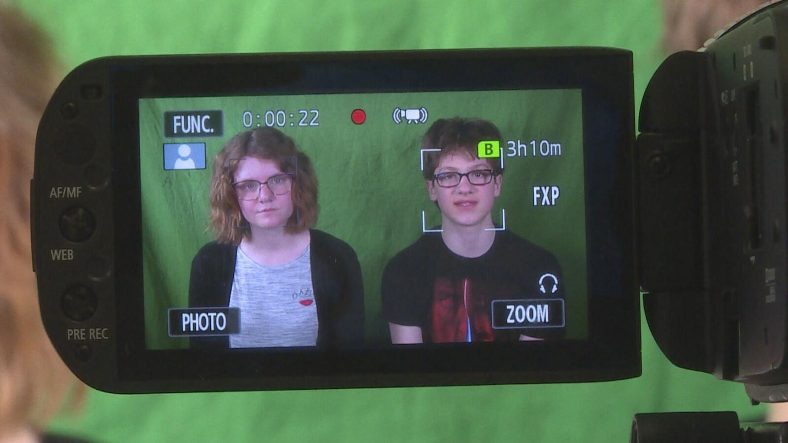 Deux élèves vus par le biais d'un écran d'une caméra
