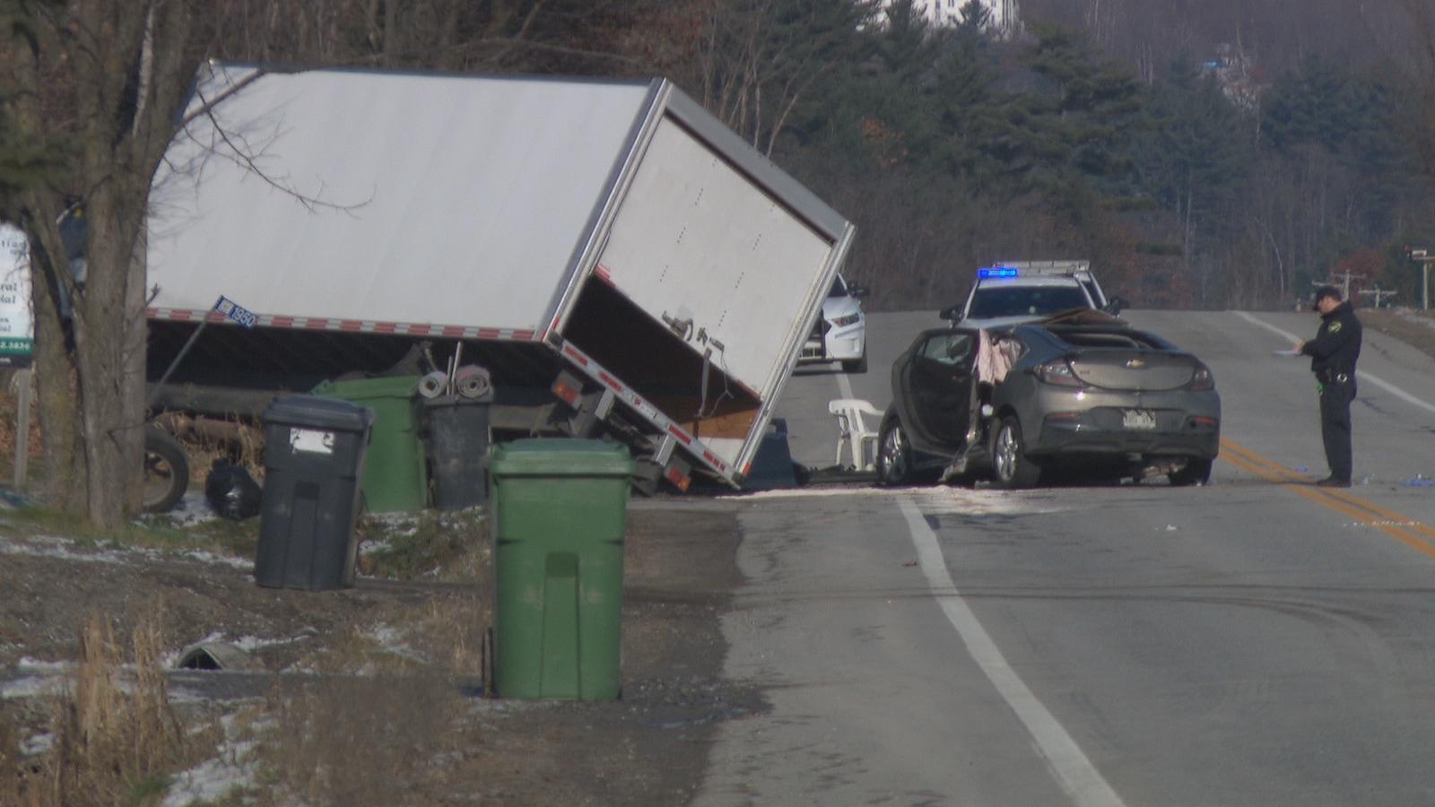 Un policier observe une voiture et un camion endommagés lors d'une collision.
