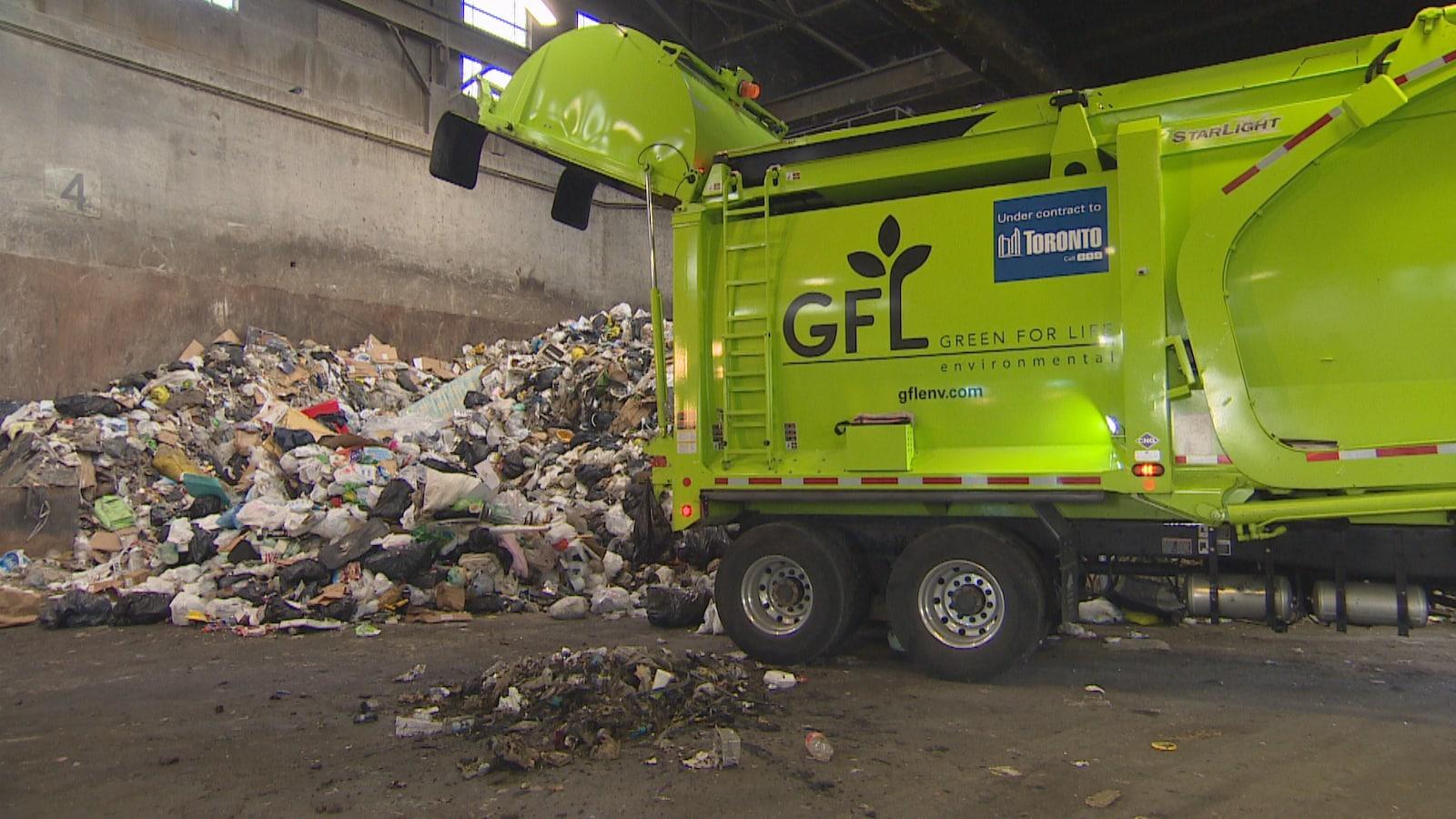Un camion à ordures vide sa cargaison sur une montage de déchets.