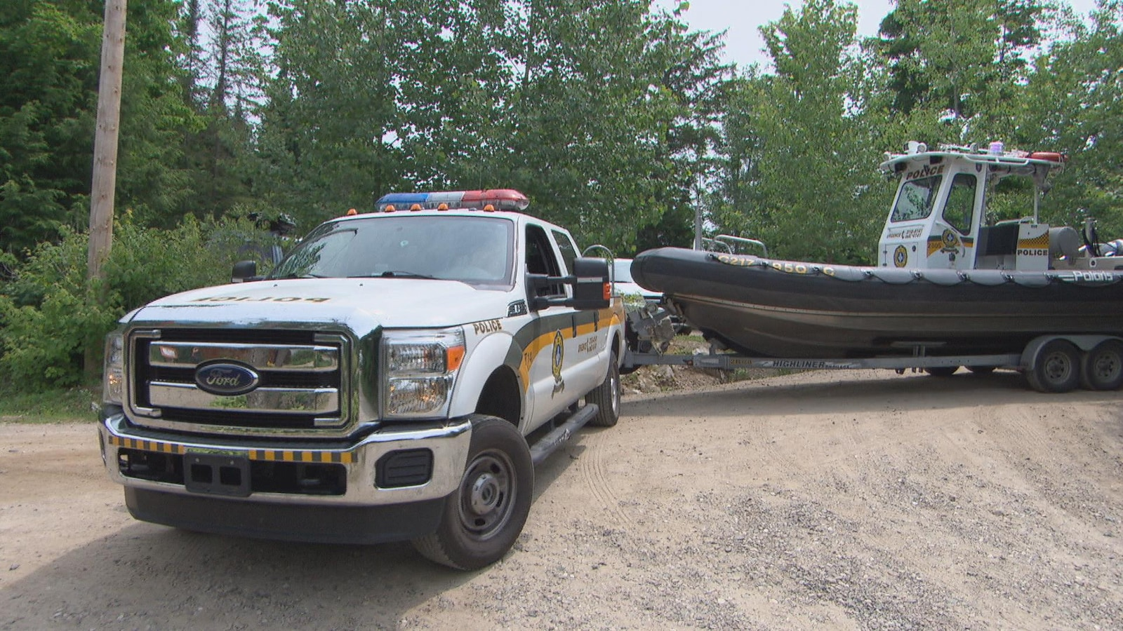Une camionnette de la Sûreté du Québec avec à sa remorque un bateau.