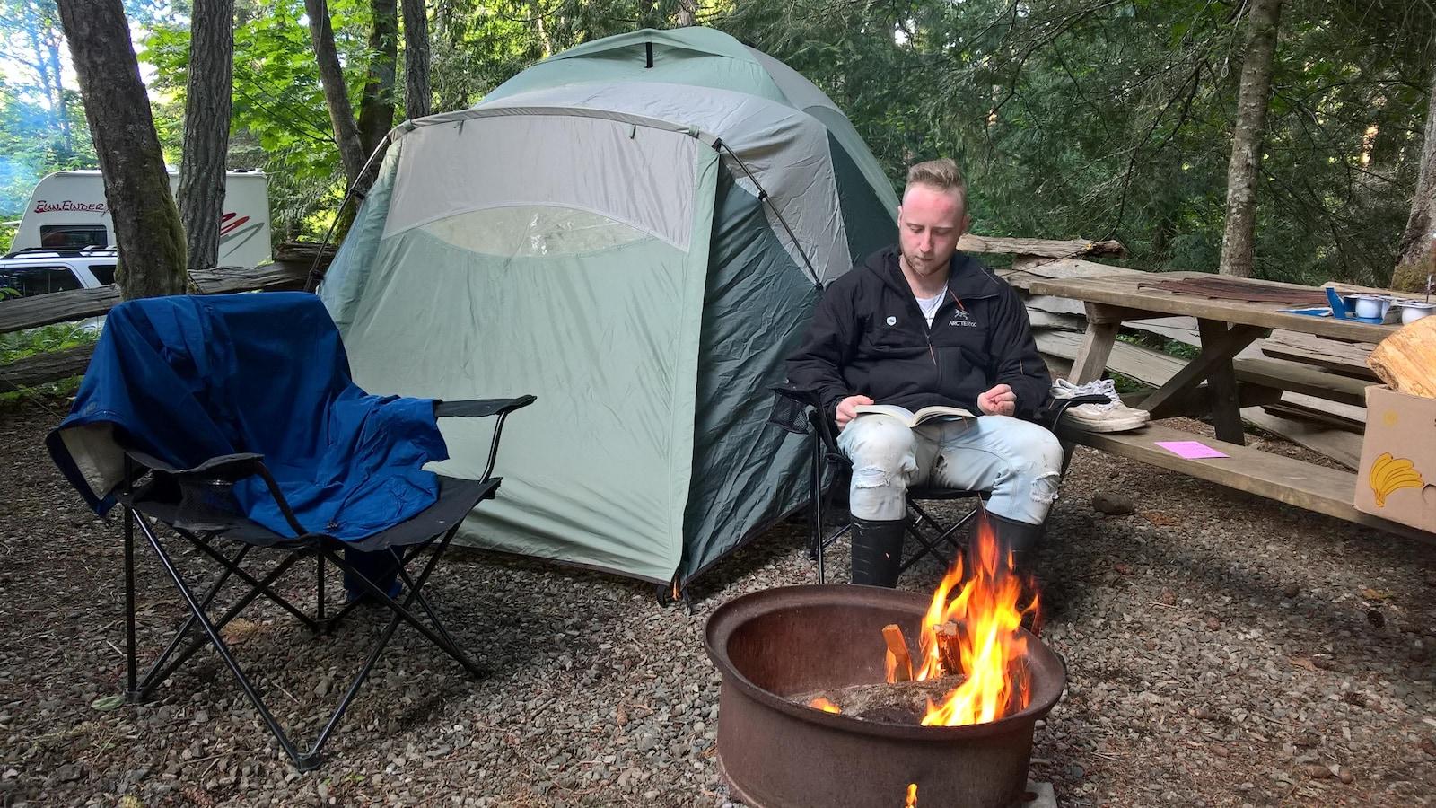 Un campeur sur l'île Salt Spring en Colombie-Britannique lit un livre entre sa tente et un feu de camp