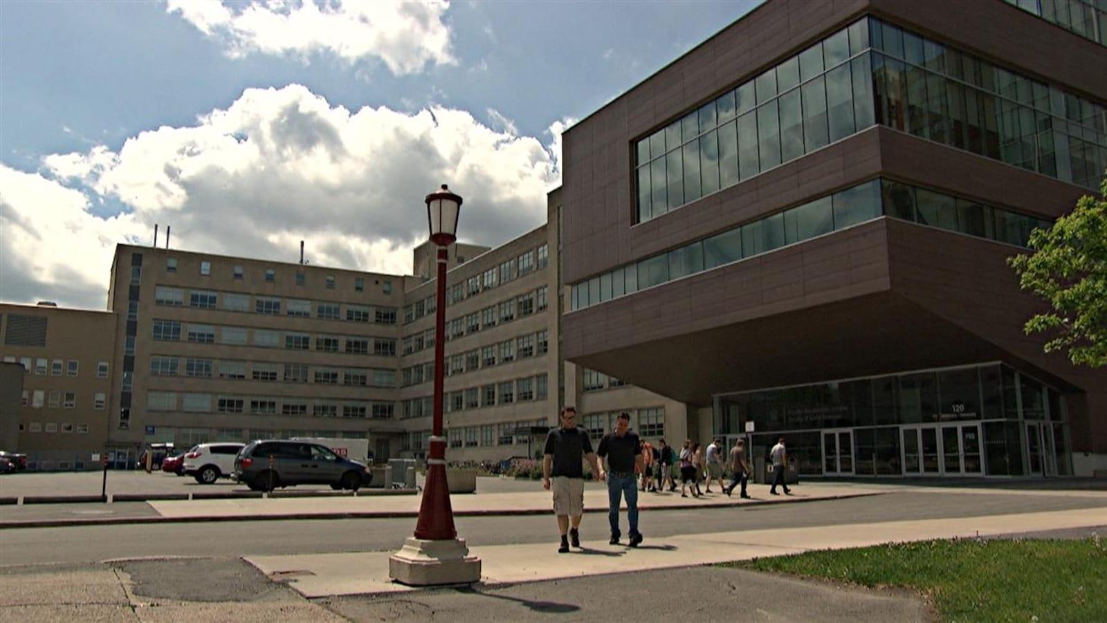 Des étudiants marchent devant un pavillon de l'université.