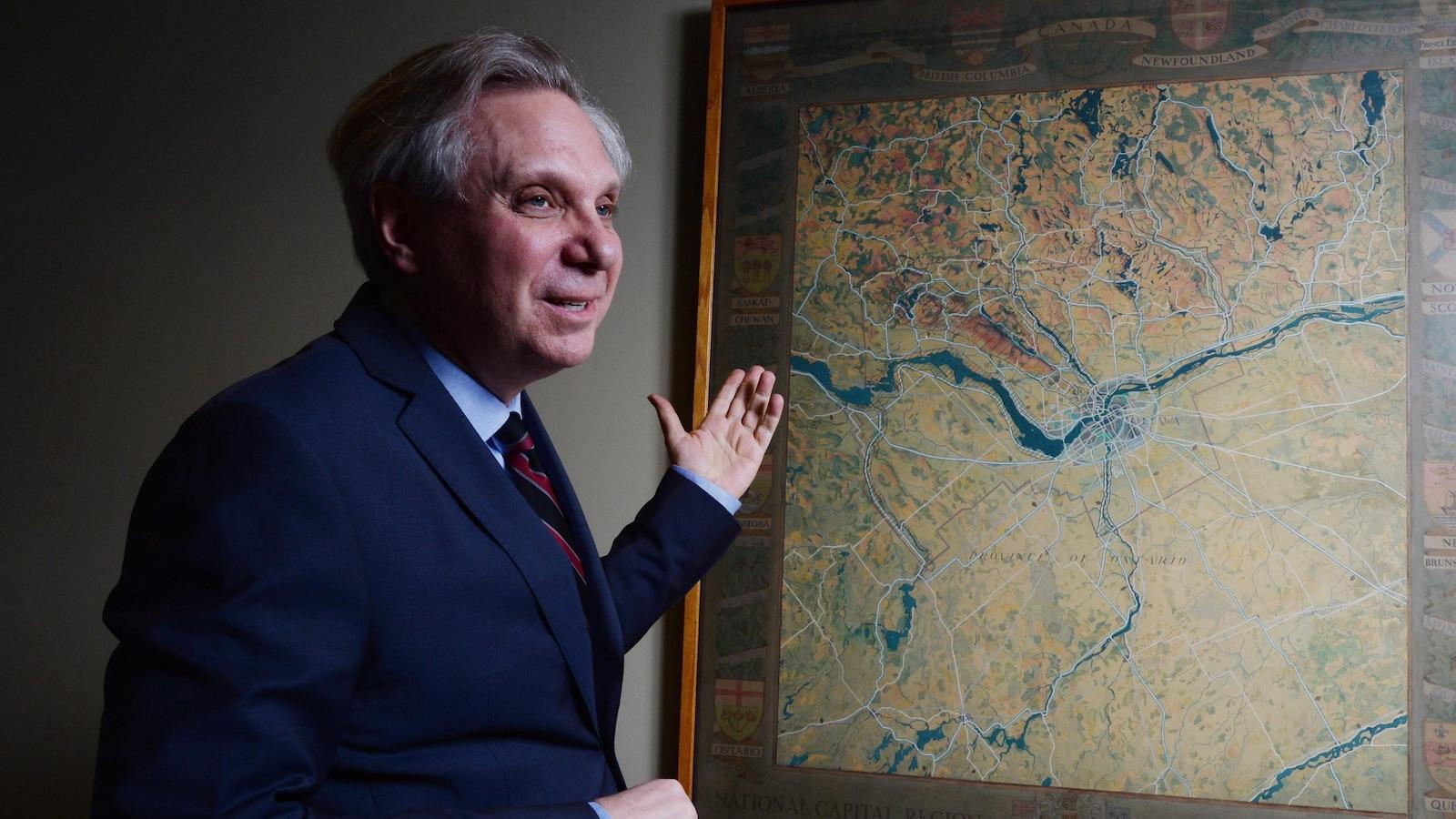 Mark Kristmanson regarde une carte de la région de la capitale nationale dans un bureau.