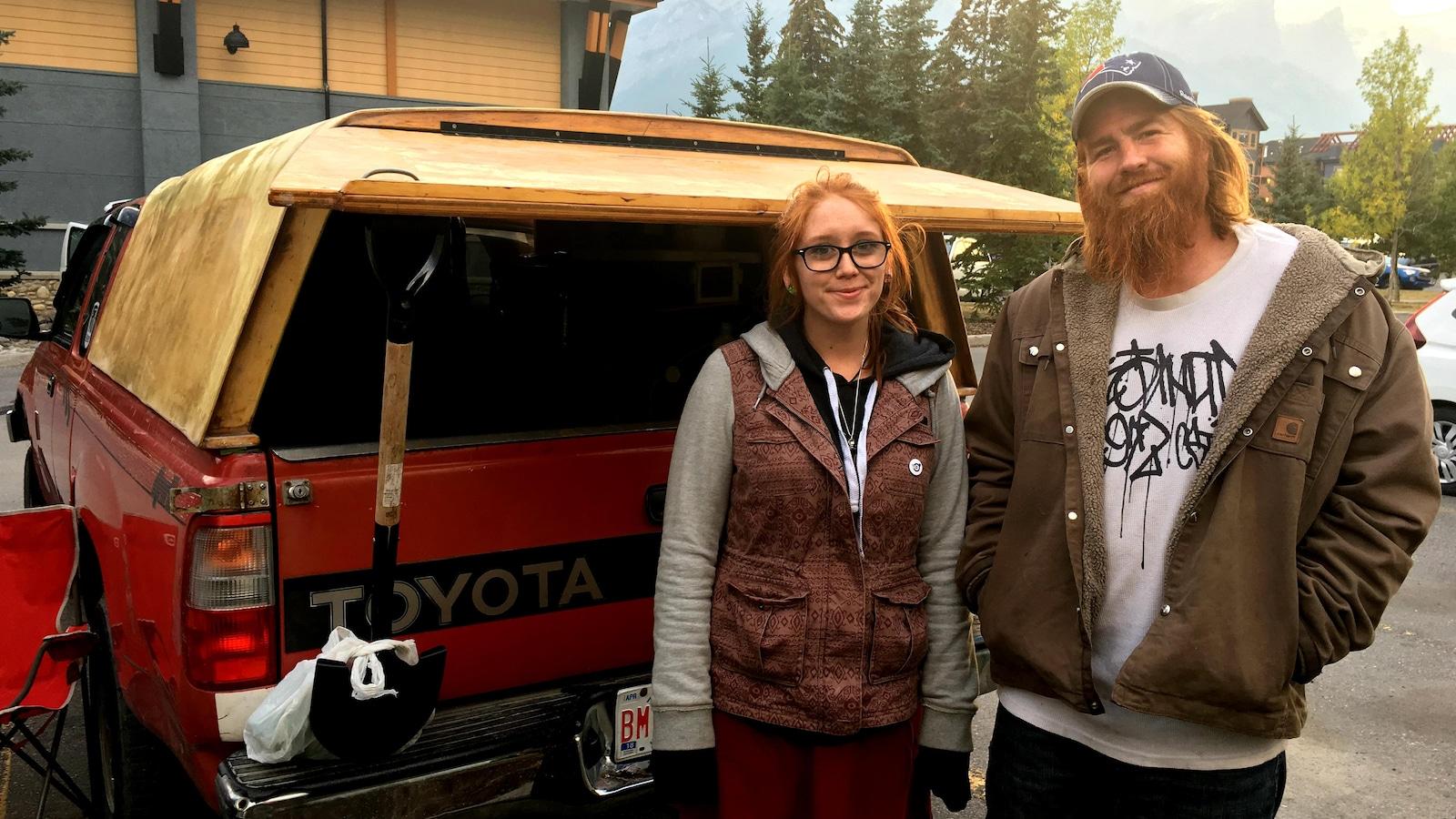 """Un homme à casquette et une femme portant des lunettes posent devant une camionnette de type """"pick-up"""" dans un stationnement avec, en arrière-plan, le mur d'un commerce, des arbres et des montagnes."""