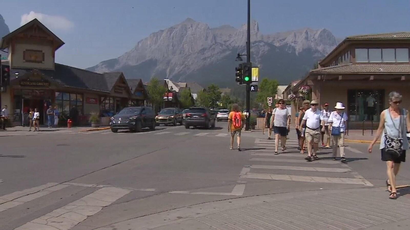 Vue sur une rue principale à Canmore. Des piétons traversent la rue et on voit les montagnes en arrière d'eux.