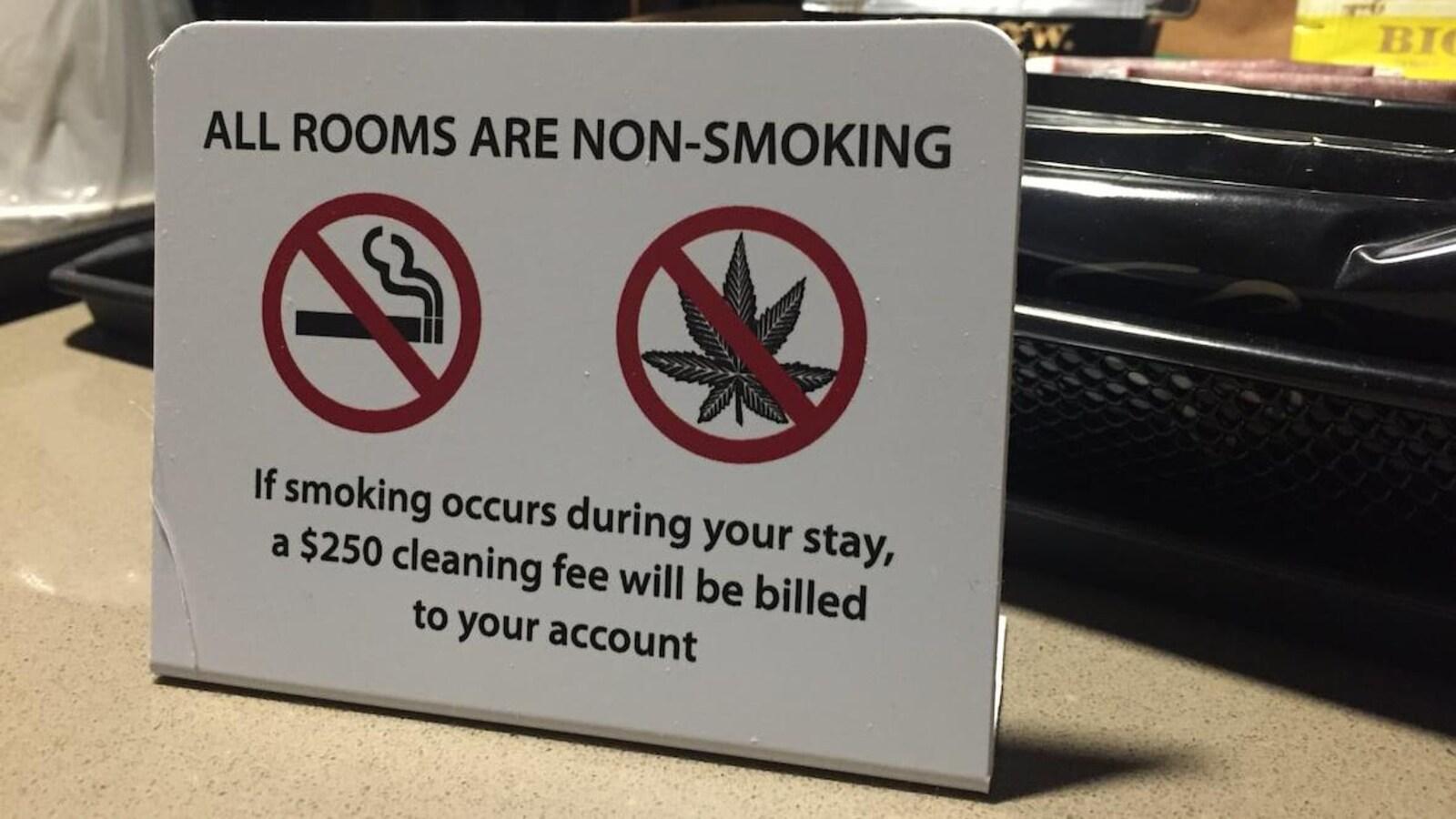 Une petite affiche indique que tout client qui fume du cannabis dans sa chambre devra payer 250 $ en frais de nettoyage.