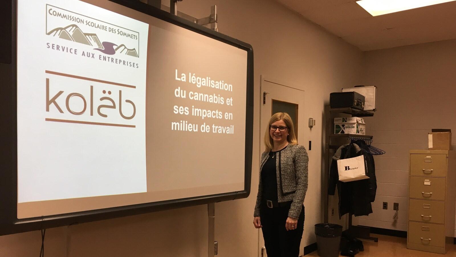 Une femme sourit à la caméra devant un tableau sur lequel est projeté le texte: «La légalisation du cannabis et ses impacts en milieu de travail» dans une salle de conférence.