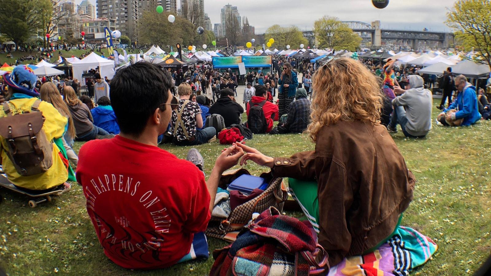 En avant-plan un homme et une femme s'échangent une cigarette de cannabis et en arrière-plan une foule et des tentes.