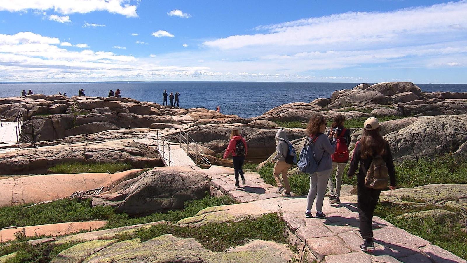 Des touristes s'approche du fleuve Saint-Laurent au Cap-de-Bon-désir à Grandes-Bergeronnes, l'endroit est privilégié pour l'observation des baleines