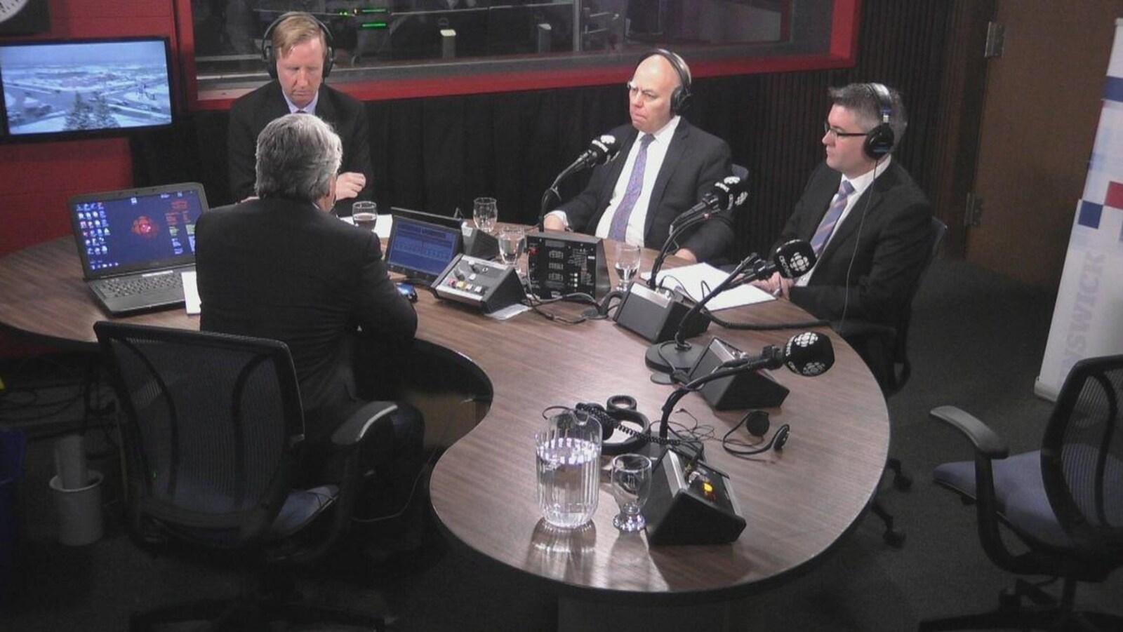 Les trois politiciens sont assis devant l'animateur dans le studio