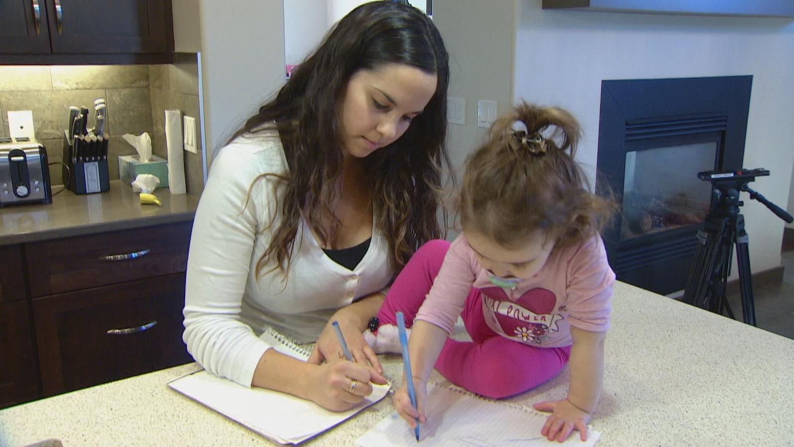 Une jeune femme et une petite fille écrivent chacune sur une feuille de papier, dans une cuisine.