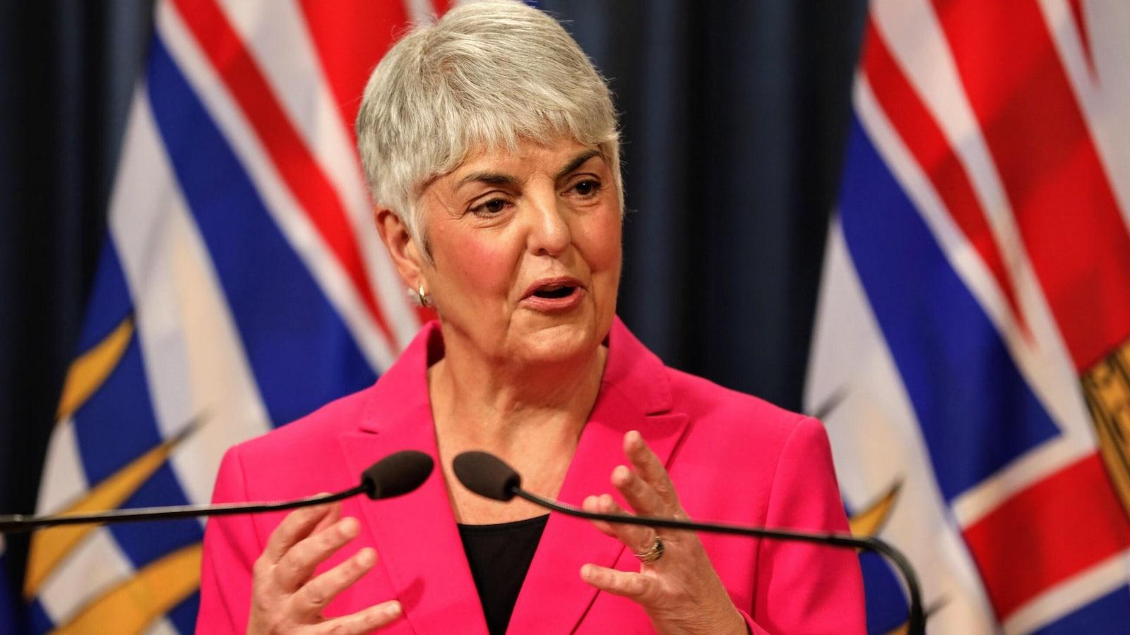 La ministre des Finances Carole James, une femme aux cheveux courts et blancs qui porte un veston rose, se trouve devant des micros. Derrière elle. se trouve un drapeau de la Colombie-Britannique.