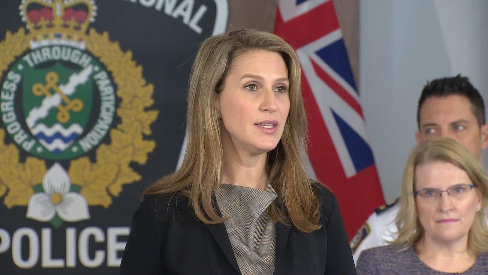 Photo d'une femme debout aux cheveux longs portant un tailleur noir devant une effigie de la police