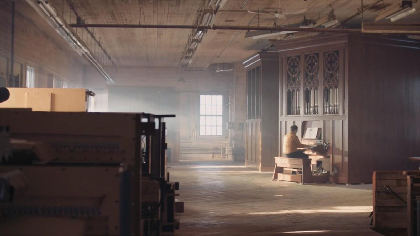Un homme est assis à un orgue au fond des ateliers de Casavant Frères.