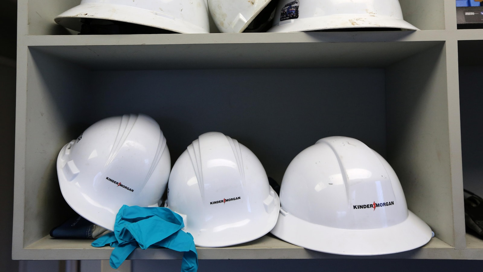 Six casques de protection blancs sont rangés sur deux étagères dans la salle de contrôle de l'entreprise en Colombie-Britannique