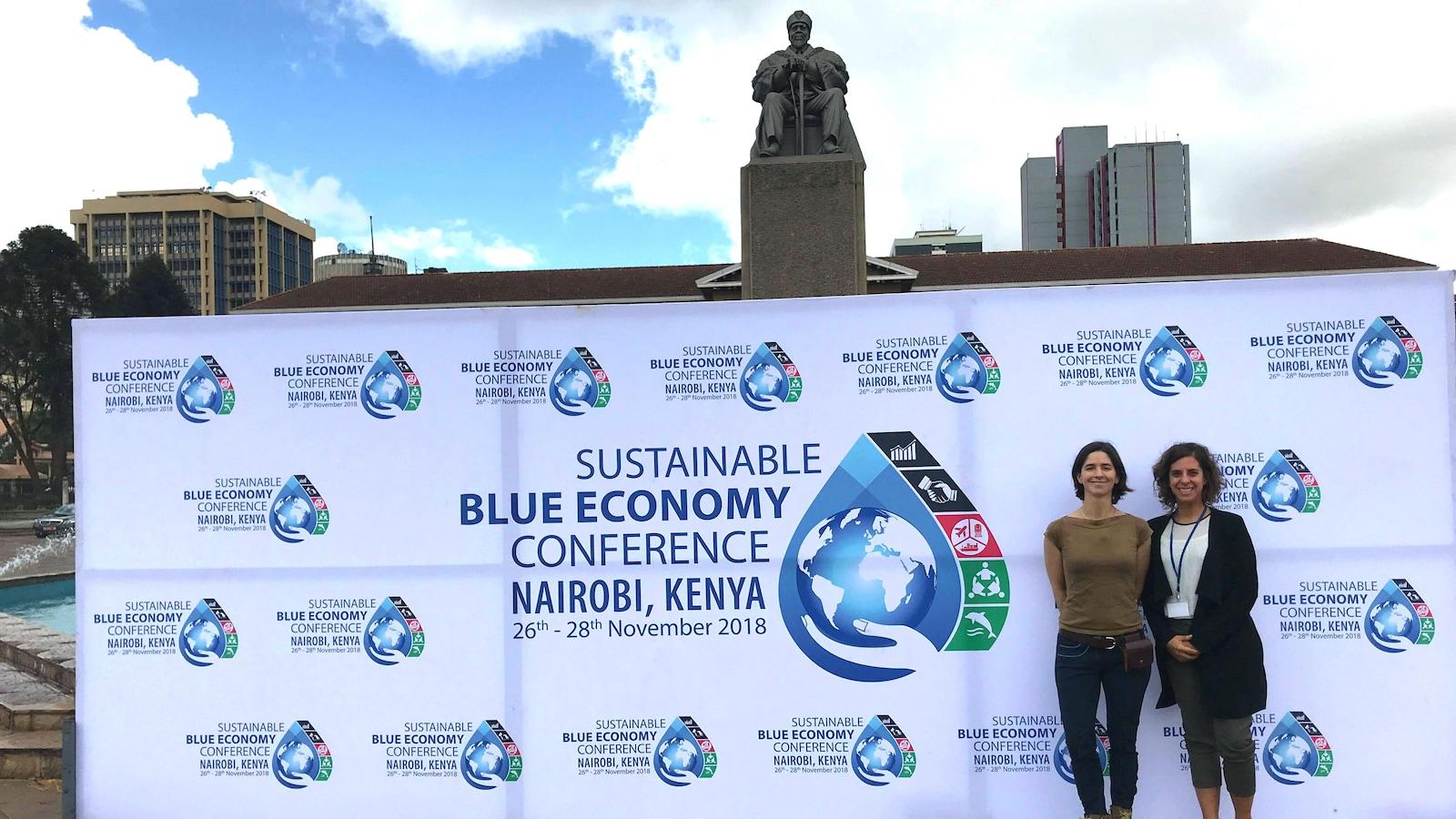 Catherine Lambert-Koizumi et Noémie Giguère devant une banderole de la Conférence sur l'économie bleue durable