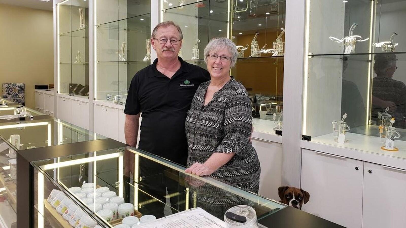 Celeste Gerber et son mari se tiennent debout en souriant devant le comptoir de leur magasin de cannabis à Swift Current