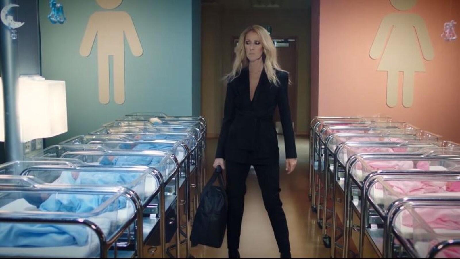 La chanteuse habillée de noir est entouré de bébés vêtus de rose et de bleu.